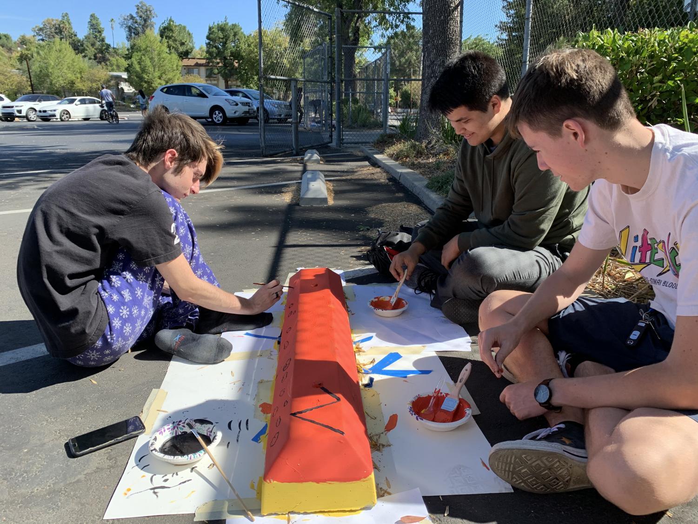 Maxwell Kozlov, Devon Oda, and Ian Tuohy help work on Ian's parking bump.