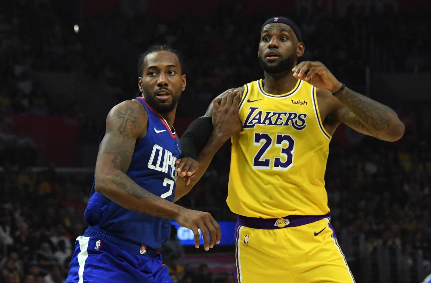 Lakers forward LeBron James fights for position against Clippers forward Kawhi Leonard.
