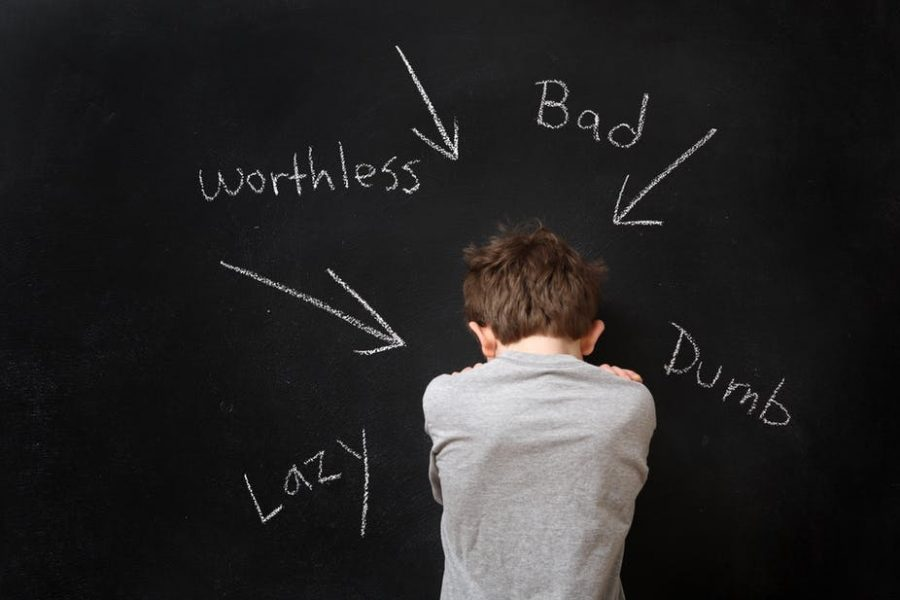 A boy standing in front of a chalk board with hurtful labels being directed at him.